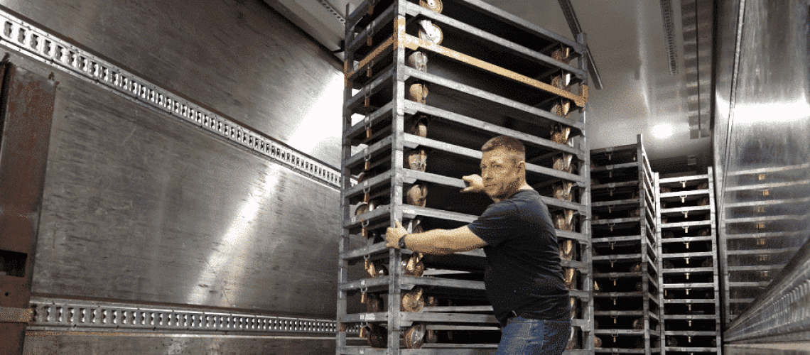 Driver handling stacked CC Container bases in truck